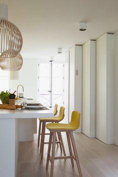 Warm scandinavisch: houten vloer, gele stoelen, houten lamp Secto Design. Kalb Lempereur : Interiors