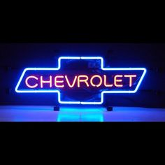 The word Chevrolet appears in red neon and the Chevy Bowtie is outlined in blue. The glass tubes are supported by a black fi Chevrolet Silverado, Chevrolet Corvette, Neon Light Signs, Neon Signs, Chevy Girl, Sign Lighting, Beer Bar, Camaro Ss, Car Manufacturers