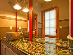 what a neat look for a bathroom sink - rocks under glass for a counter-top!