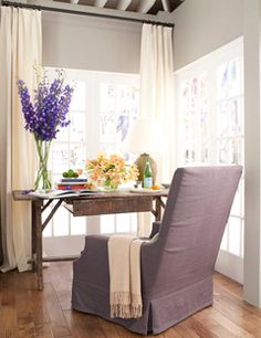 Simply gorgeous design in Ina Garten's kitchen barn: soft gray paint, antique rustic table, comfy chair, big windows and fresh flowers