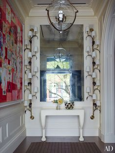 New York Townhouse Restored by Peter Pennoyer and Shawn Henderson  Sconces in the style of Paavo Tynell are mounted on either side of the entrance hall's vintage John Dickinson console; the collage at left is by George Condo.