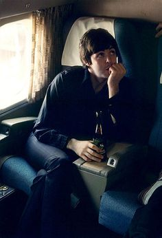 Paul McCartney drinking a beer in flight as Beatles tour USA in the mid-1960s