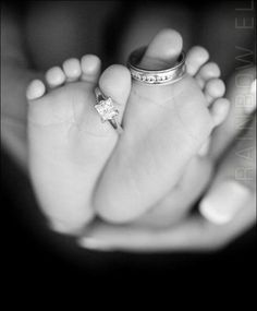 A new born baby with the parents rings on the toes