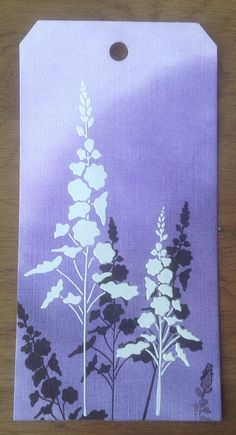 handmade tag ... stenciled flower silhouettes on sponged background of lighter tone ... same stencil used to finish off in white texture paste ... luv the look ...