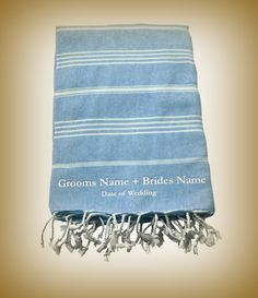 Large cotton beach towel customised and embroidered in white with the groom and brides name in a classic font. Dreaming of the ultimate casual and intimate beach wedding. If you are planning a fabulous beach or location wedding this year these towels make a wonderful and memorable wedding party gift. Your guests that have travelled to be with you on your most special day will have a lovely and practical gift to use on holiday and to remember your nuptials for many years to come.