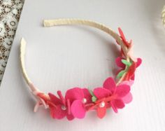 This beautiful headband with felt flowers placing on the side, and wraps around with yellow grosgrain ribbon. This headband is absolutely lovely and