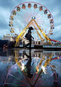CALGARY, JULY 10, 2011: A cowgirl walks past a ferris wheel at the Calgary Stampede. (Photo by Mario Tama/Getty Images)