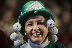 Una mujer ataviada con un sombrero de disfraces, en el Teatro Real, lleva adosado uno de los números que juega en el sorteo extraordinario de la lotería de Navidad 2014.