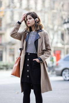 Edited the label striped top, Zara trench coat, Stradivarius leather jacket, Edited the label button skirt, Chloé booties, Mansur Gavriel bucket bag, Frends Layla headphones, Cluse watch