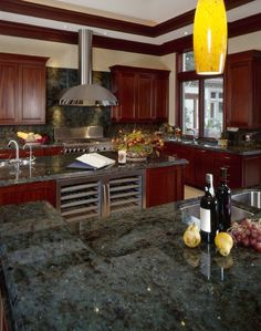 Dark stone countertops complement richly stained natural wood cabinetry. The space also includes dual wine chillers and blown glass light pendants.