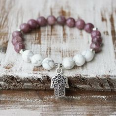A hamsa healing bracelet made with lepidolite and howlite. Handcrafted with love and intention in the U.S.A. Carefully strung on latex-free elastic cord to make it easier putting on and taking off. Sm