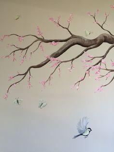 Muurschildering van een tak met roze bloesem, koolmeesjes en vlinders