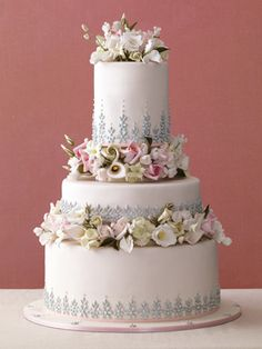 A Formal Floral Wedding Cake    Three-tiered dusty pink fondant wedding cake accented with silver dragees and sugar flowers.