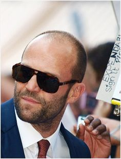 Jason Statham wearing large shades, he looks like he is lookin'g for someone, forget it girls, he has eyes only for PAM