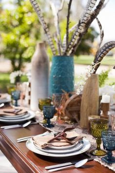 thanksgiving boho tablescape with wood vases, vintage glass, feathers