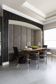 A breakfast niche with custom-stained wood design that a carpenter built piece by piece. The inside of the niche is covered in grey tufting.