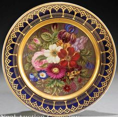 A Paris porcelain plate~in the high Gothic Revival style Depicting a floral still life~Gilt banding~Heavily gilded Origin France~Circa 1830-1860