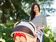 Beautiful Woman Pushing Stroller In Park - Stock Photo - Images
