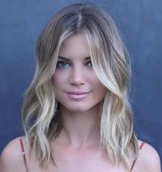 Medium Wavy Hairstyle | #21: Balayage Waves. A round face with a low forehead looks perfect with a medium haircut and no bangs. Not having bangs adds visual length to the face. When the front pieces are styled forward and to the sides, it creates a mysterious look. Complete the style with face-framing highlights.