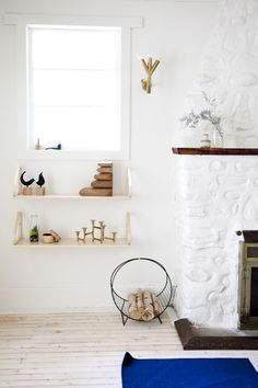 The original brick fireplace was painted white. On the wall is a vintage Swedish sconce by Knut Hallgren.