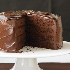 If you like a very tall layer cake, double all of the ingredients for four layers instead of two. Preheat the oven to 325°F. Butter the bottoms and sides of two 9 by 2-inch round cake pans, and line with parchment paper. To make the cake, in the top of a double boiler or in a heatproof bowl over barely simmering water, melt together 4 ounces (1 bar) of the bittersweet chocolate, butter, sugar, and corn syrup, stirring occasionally until smooth. Remove from the heat and set aside. In a medium…