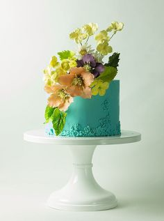 The color palette used for this cake is beautiful. The placement of the floral decorations in relation to the icing details really draws one's eyes through the whole cake. Love the look of the intricate same-color icing detail.