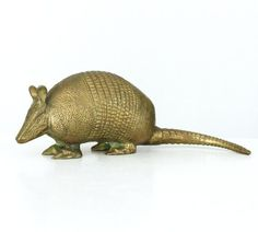 Vintage brass armadillo figurine. Highly detailed cast brass armadillo with an intricately textured surface and long, curved tail. Rich, gold-tone color with beautiful patina. A very unique piece of decor, its also quite heavy and would make a great paperweight or doorstop. Unsigned though there is a faint remnant from an original sticker on the underside. Measures approximately 9 long from the nose to the curve in the tail x 3 1/2 high x 2 1/2 wide. Excellent vintage condition with...