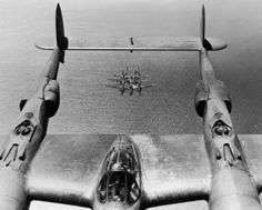 circa 1943: Formation of twin engine, double fuselage, U.S. fighter airplanes is visible through the twin tails of one of the aircraft as they fly over the Pacific Ocean on the Pacific Front during World War II. (Photo by Hulton Archive/Getty Images)