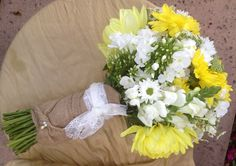 Yellow and White Country Chic bouquet. Yellow Dahlias, Yellow Mums, Mini daisies, chamomile. Wrapped in Burlap, with a swatch of fabric from the bride's gown.