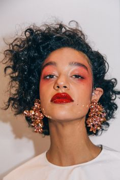 red eyes, red lips and copper statement earrings