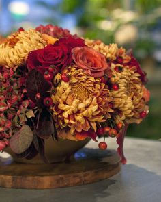 "An attractive array of colorful flowers are joined with beautiful fall leaves to create this stunning holiday centerpiece. Featured Flowers Hydrangeas Rosehips Fall leaves Martha Stewart ""Blaze"" Chrysanthemums Flowers in the Martha Stewart Autumn Rose Medley: Orange milva roses Bi-color orange and yellow cherry brandy roses Deep-red black magic roses Reddish-brown terra cotta roses"