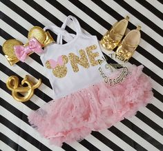 2pc Pink and Gold Glitter Minnie One Year Old Birthday Tutu Dresses For Toddler GirlsLet us add a little or a lot of shine to your little birthday angel's life with our New and Exclusive glitter minnie inspired one year old birthday tutu dresses. This tutu dress makes the perfect minnie themed birthday outfit! Designed with a gold glitter two with mint bow on a fluffy pink tutu dress with silver sparkles. Your little one will definitely be the sparkle in your eye on their very special day...