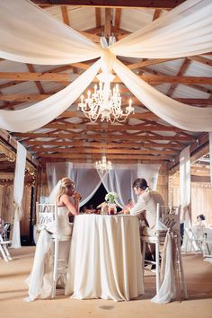 Rustic chic wedding reception decor - draped fabric from ceiling + crystal chandelier {Frozen Exposure Photography + Videography}