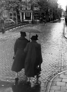1950's. Two women in the rain near the bridge over the Herengracht in the Jordaan in Amsterdam. Photo Maria Austria Institute / Kees Scherer #amsterdam #1950 #herengracht