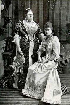 ''Princess Mary of Teck with her mother, Princess Mary Adelaide, Duchess of Teck 1893''. The Duchess is a big lady but she's not letting go of her waist. Getting corsets to meet occasionally involved a knee in the small of the back as the laces were tugged through. HRH's maid must have had strong biceps.