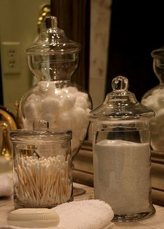 Utilize glass apothecary jars and canisters (from dollar stores) in bathrooms and fill with inexpensive bath items such as cotton balls, bath salts, soaps, etc.