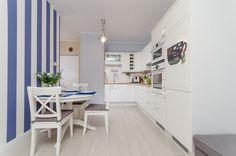 Pasiasta niebieska tapeta ożywiła tę stonowaną białą kuchnię z uroczym aneksem jadalnianym w stylu prowansalskim / Provence - style dining room idea.