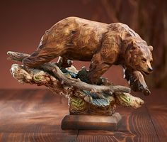 """Add this sensitive portrait of a noble brown bear to your cabin or lodge for the perfect touch of Nature. Sculpture is positioned on an artistically arranged base of sculpted driftwood and stone. Cold cast and hand painted. 8-1/2""""H."""