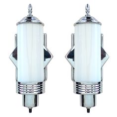 This is an excellent original pair of Art Deco Sconces. The chrome frames hold the original white glass inserts. They are really clean with great style.