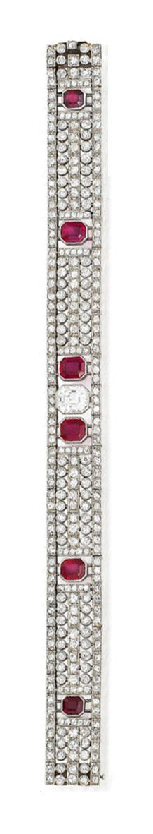An art deco ruby and diamond bracelet, circa 1930  The highly articulated pierced strap composed of courses of millegrain-set single-cut diamonds, with a step-cut diamond to the centre, further accented by six graduated step-cut rubies, principal diamond approximately 2.25 carats, remaining diamonds approximately 6.15 carats total, unsigned, French assay marks, length 18.2cm, fitted case by Spink