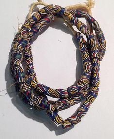 """These strands of African sand cast beads are approx. 23-25"""" long. The average bead measures 16.5 mm long x 9 mm in diameter. These beads are also available in black åÊ(as opposed to dark blue, pictured here) åÊwith multicolor stripes, and can be found in a separate product listing within the Sand Cast Bead category."""