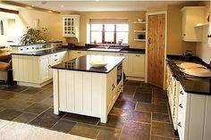 slate floors, white cabinets, black granite