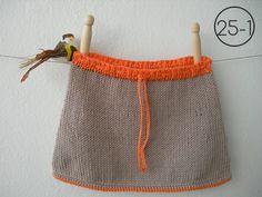 Falda en punto jersey en color visón y remates en elástico de 1 y ganchillo en color naranja.