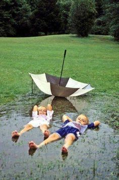 Love A Rainy Day. Kids lying in a mud puddle, water puddle actually ditched the umbrella for fun, so cute!