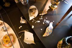 A toppled vase has smashed to reveal a hoard of stolen silver spoons, netsuke and jewellery. Flying skullships constructed from animal skulls, silver and broken ceramics are flown by enslaved insects. They deposit stolen objects into vases as they fly past. An angry swarm of honey bees, controlled by the fairies, spews from other vases.