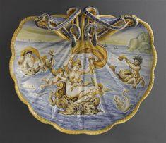 Musée d'Ecouen. Bassin en forme de coquille surmontée de 2 serpents enroulés en haut-relief (Vénus marine ?) ECL1151. Décor mythologique: Amphitride et tritons. Avers 18°s. CASTELLI (origine). Ht: 0.13 Largeur: 0. m Profondeur: 0.435 m.