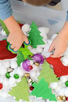 A child using scoop tongs to pick up items in the sensory bin.