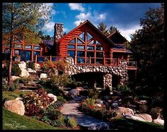 A bright blue sky and beautiful landscaping enhance this already gorgeous cedar and stone home!