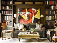 i love this couch, the bookshelves, the bright painting, the ottoman/table, the carpet...