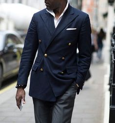 Double breasted Navy suit with a touch of white pocket square. Style tip: With a double breasted suit, always fasten the middle button and leave the bottom undone.